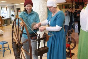 Luceta showing a museum patron how to spin fiber on a wheel.